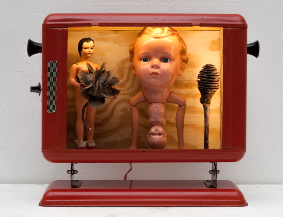 Eschumano 3, metal, wood, dolls parts, 38 x 32 x 12,5 cm, electricity: 230 V (Trafo), function: licht, 2013, 500 €